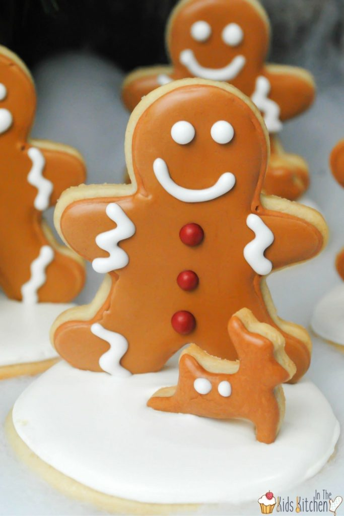 Cute and delicious gingerbread men standing on a snowy cookie - what a cute Christmas cookie idea!
