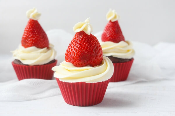 Easy Santa Hat Cupcakes that kids can help decorate! A festive holiday treat perfect for a Christmas party! Rich chocolate cake & luscious vanilla frosting.