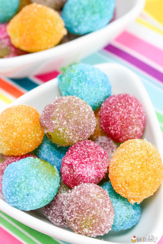 Vibrantly colored Rainbow Jello Frosted Grapes are as pretty as they are delicious! This party treat is sure to be a hit with both kids and grown-ups alike!