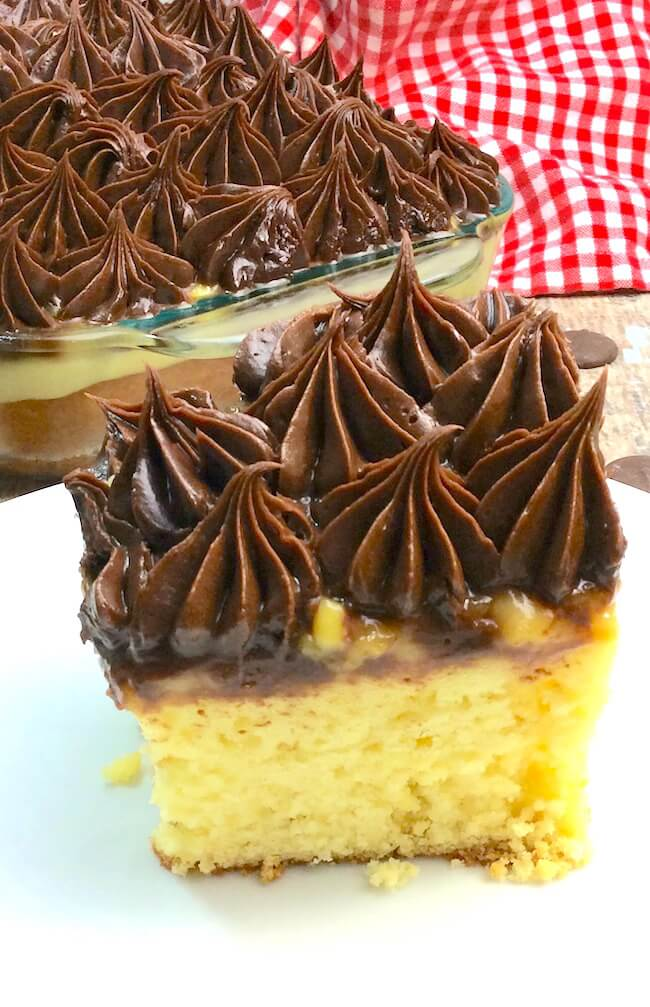 An over-the-top decadent Boston cream pie poke cake made from scratch - guaranteed to be a hit at the next potluck or birthday party!