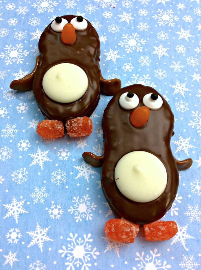 Adorable chocolate dipped Nutter Butter Penguin Cookies are just as fun to make as they are to eat! Easy kids holiday party dessert.