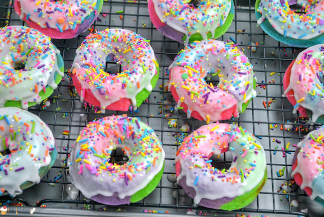 Kids will go wild for these rainbow swirled Unicorn Donuts! Easy baked donut recipe with sugar glaze - a guaranteed hit for any occasion!